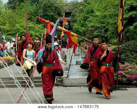 Dujiangyan China - April 24 2005: Taoist monks carrying flags walking in the gardens at Dujiangyan Historic Park