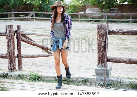 Serious attractive young woman cowgirl waking in village