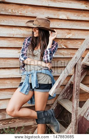 Cheerful attractive young woman cowgirl standing and smiling near the house