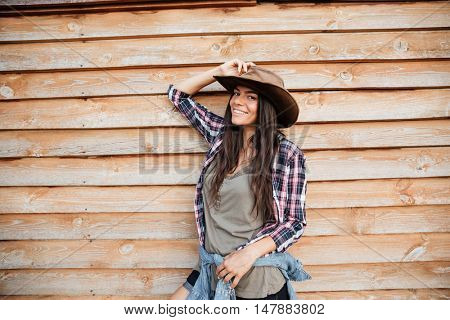 Happy attractive young woman cowgirl in plaid shirt and hat standing and smiling over wooden background