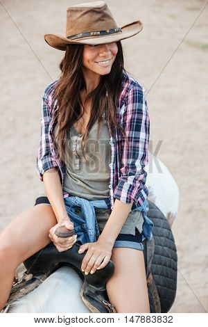 Portrait of happy pretty young woman cowgirl riding a horse outdoors