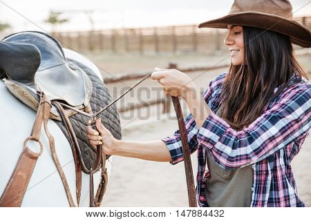 Beautiful young woman cowgirl standing and putting saddle on horse
