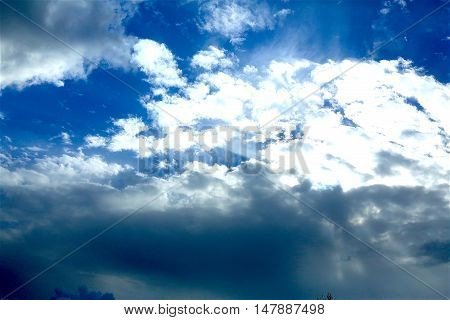 beautiful bright blue sky with white clouds illuminated by the sun