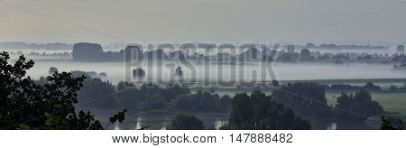 Panorama morning mist landscape. River Nederrijn with floodplains and meadows, seen from Wageningse Berg at Wageningen, The Netherlands. Short before sunrise.