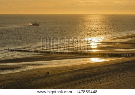 Walking on the sandy beach of Zoutelande at sunset