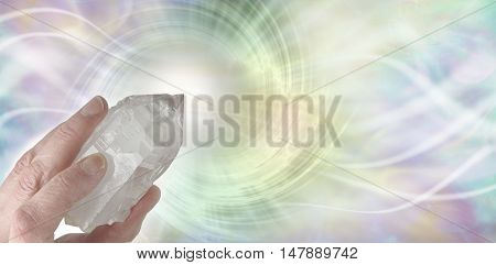 Crystal Therapy Resonance - Female hand pointing a clear quartz terminated crystal upwards on a light pastel rainbow colored  spiraling  vortex background with copy space