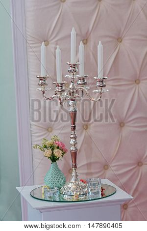 Silver candlestick in a classic style and a bouquet. Wedding decorations