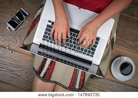Woman with laptop, smartphone and coffee sitting on wooden floor. Top view