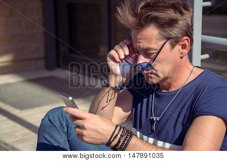 Man Reads The Message From The Phone. Intense Eyes