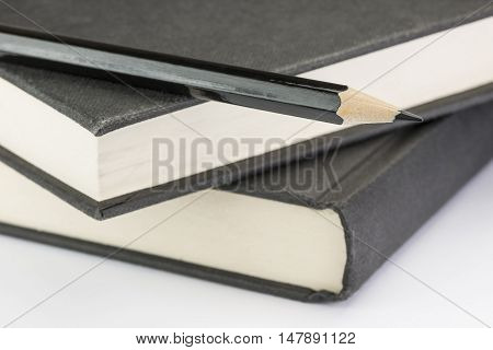 Black wooden pencil to write on two black stacked write notebooks