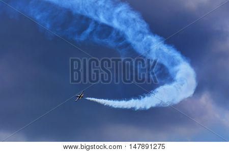 Airplane with vapor stripes in the blue sky