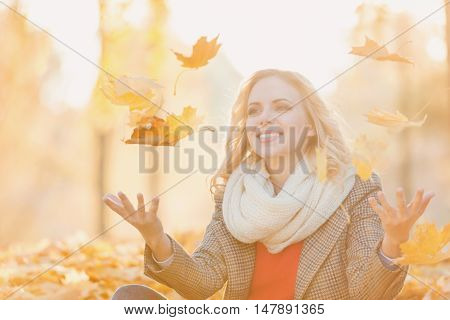 Beautiful young woman in checked coat, red sweater and white knitted scarf in autumn park sitting on the ground, throwing yellow tree leaves in the air