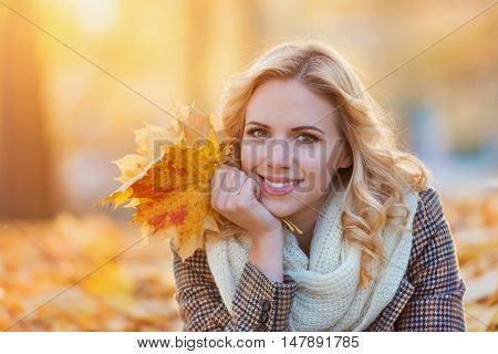 Beautiful young woman in checked coat and white knitted scarf in autumn park sitting on the ground, holdind yellow tree leaves in her hands