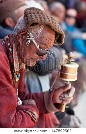 LAMAYURU, INDIA - JUNE 17, 2012: Man with prayer wheel praying in Lamayuru Gompa during Yuru Kabgyat festival.