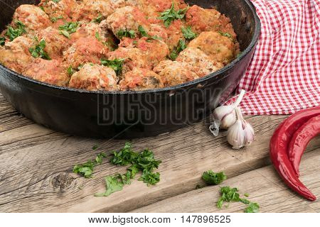 meat balls with herbs in pan on wooden rustic background. Selective focus.