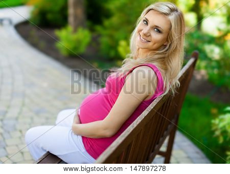 Portrait of a Pregnant Woman in a Park