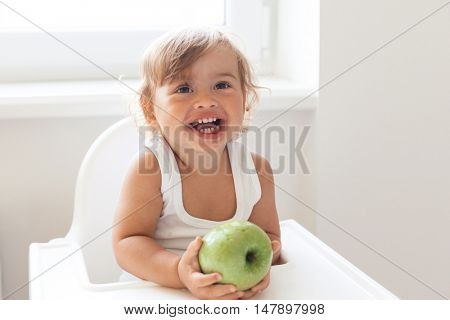 Cute baby 1,4 years old sitting on high children chair and eating fruit alone in white kitchen