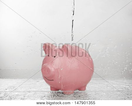 Pink piggy bank with jet of water on light background. Saving water concept