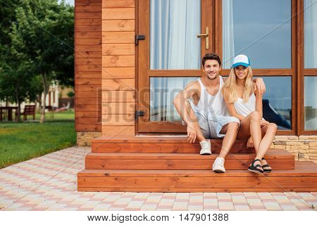 Happy young couple sitting and hugging on porch of the house