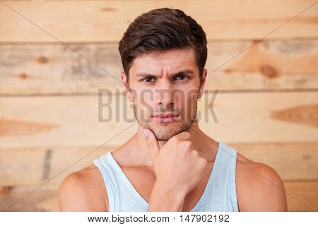 Portrait of thoughtful serious young man touching his chin over wooden background