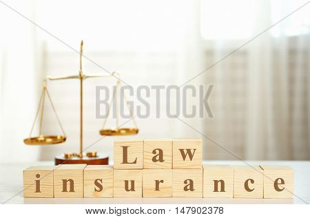 Wooden cubes with phrase LAW INSURANCE and scales on a table