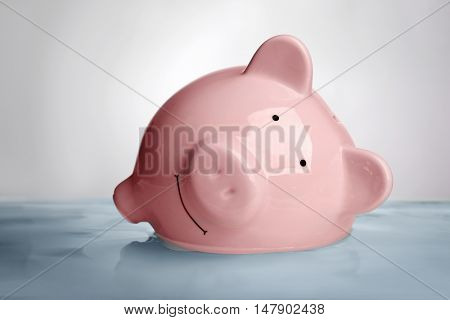 Pink piggy bank in water on light background. Saving water concept
