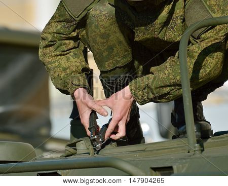The soldier puts the seal on the hatch of the war machine.