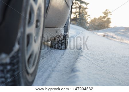Car wheels leaving tracks on a snowy road