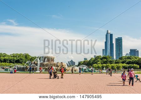 Chicago, USA - May 30, 2016: Buckingham Memorial Fountains in Grant Park in Illinois with people walking on a hot summer day with skycrapers.