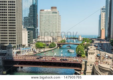 Chicago, USA - May 30, 2016: Aerial view of Lake Michigan, DuSable bridge and Wacker Drive with many skyscrapers, people, cars and boats on downtown river.