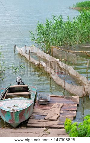 fish farm. Motor boat fishing equipment and network with young fish on the lake.