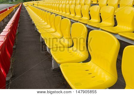 yellow-red grandstand without people at the stadium