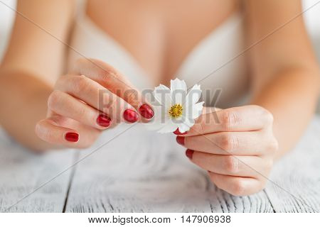 Woman in bra guesses on a chamomile flower