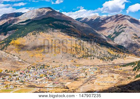 Aerial view of Silverton, Colorado in the fall with coal train and smoke with mountains and yellow aspen trees in the fall and clouds casting shadows