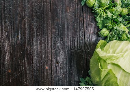 Green cabbage, broccoli and brussel sprouts on the dark wooden surface