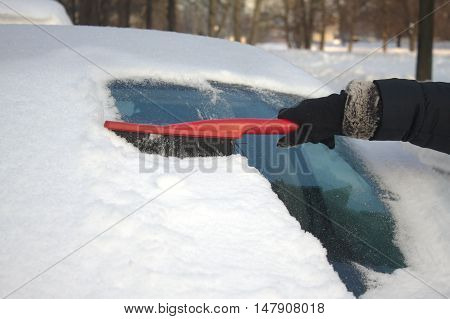 Woman's hand in black garment brushing snow from car windshield closeup vertical view