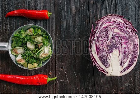 Red cabbage, broccoli, brussel sprouts and chili peppers on the dark wooden surface