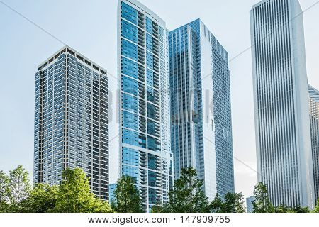 Chicago, USA - May 30, 2016: Downtown residential skyscrapers in Lake Shore East Park with green trees.