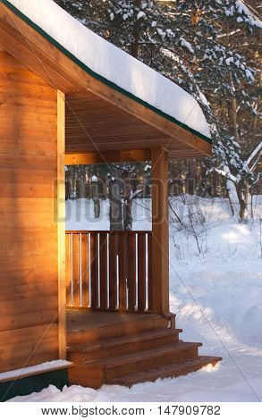 Porch of a wooden house in the woods on winter day