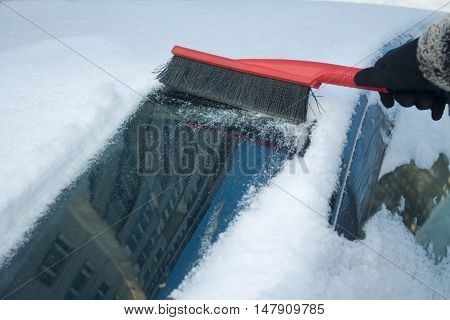 Woman's hand in black garment removes snow from car windshield in winter day closeup
