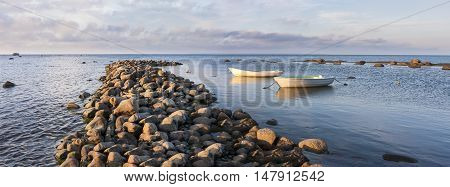 Two white oaring boats behind cobble stone pier in sea at sunset