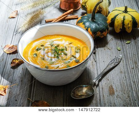 Roasted pumpkin soup with cream and pumpkin seeds on wooden background. Selective focus.