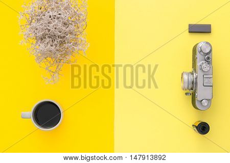 Work space on yellow table of a creative designer or photographer with laptop tablet camera and other objects of inspiration and copy space. Stylish home studio concept of technology trends. View from above.