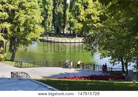 Bucharest, ROMANIA - August 14 2016: Central area of Alexandru Ioan Cuza park or IOR park on a peaceful summer afternoon. People relaxing in the sun or riding bicycles. BUCHAREST -August 14 2016