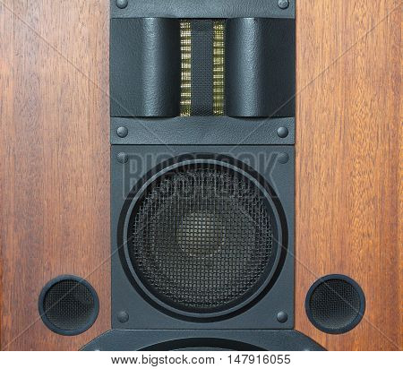 Loud speaker system with wood finish and metal black grills front view closeup