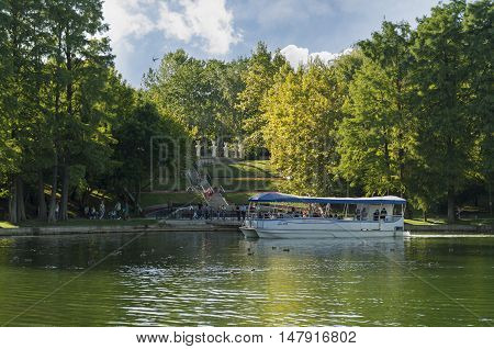 Bucharest, ROMANIA - August 14 2016: People taking a tour of the park on a boat or strolling through IOR park. BUCHAREST -August 14 2016