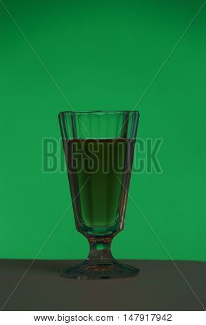 Crystal glass with a drink on a green background