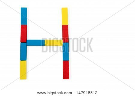 Capital letter H made up of different color wooden rectangular blocks isolated on a white background