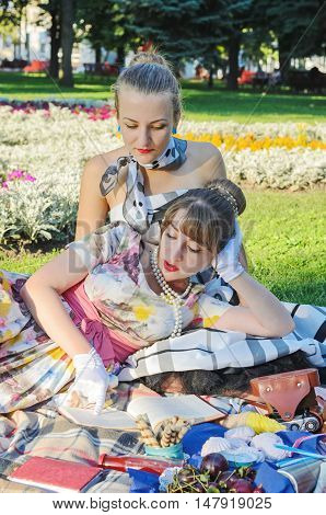 Two retro-style girls on a summer picnic reading a book aloud