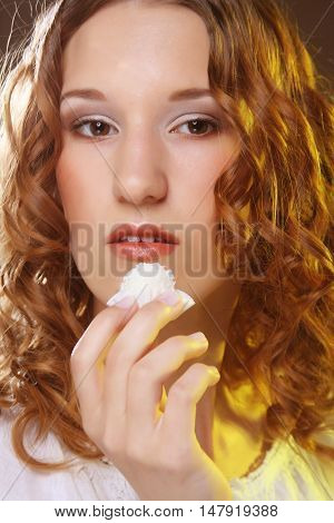 beauty portrait of a cute  girl in act to eat a candy with cocoanut